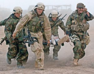 U.S. troops enduring a sandstorm while transporting an injured comrade.